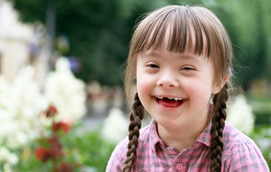 Young girl with down syndrome smiles for a picture