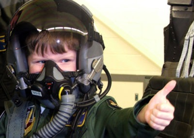 child wearing a flight mask gives thumbs up